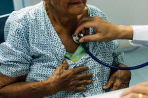 Male doctor using a stethoscope to listen to elderly woman's breathing